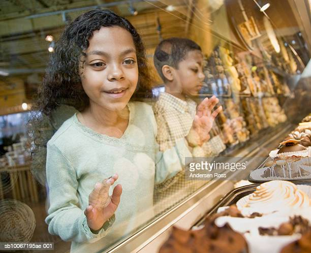 boy and girl (8-11) looking at pastries in window display - pastry dough stock pictures, royalty-free photos & images
