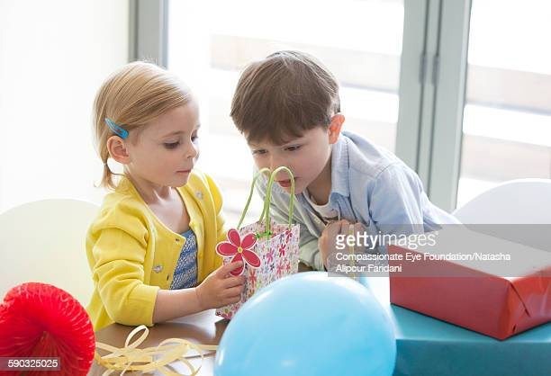 """boy and girl looking at presents at birthday - """"compassionate eye"""" stock pictures, royalty-free photos & images"""