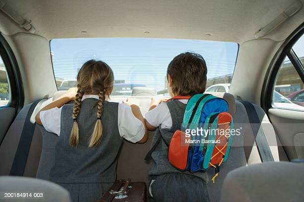 Boy and girl (5-7) looking out back window in car, rear view