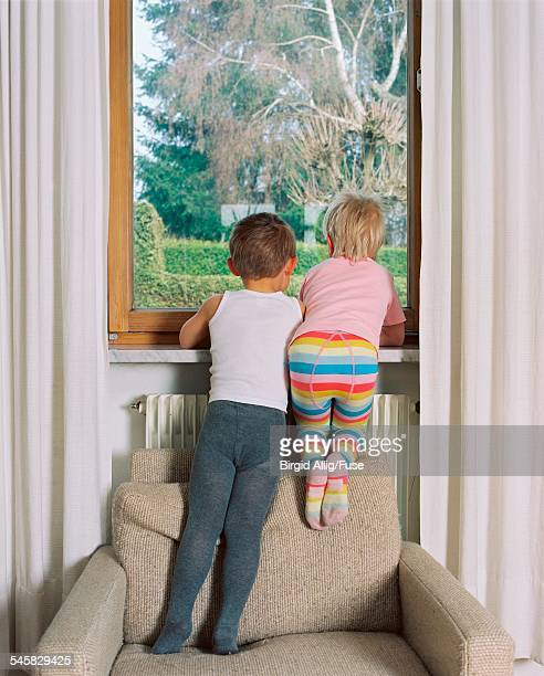 boy and girl looking out of window - boys wearing tights stock photos and pictures