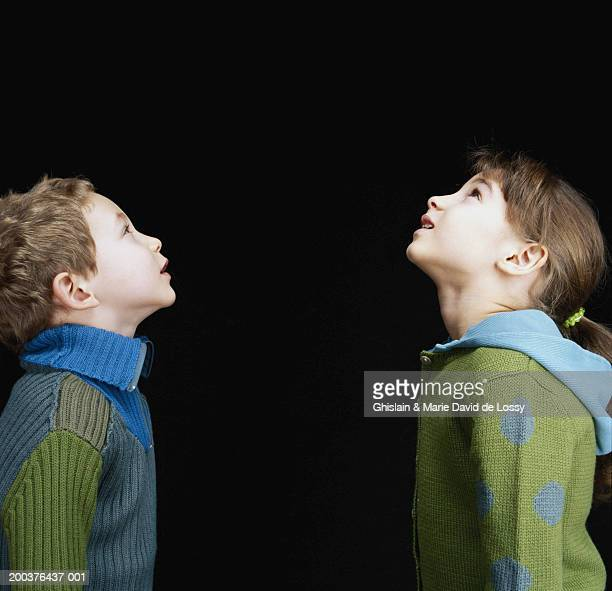 Boy and girl (3-6) looking upwards, side view