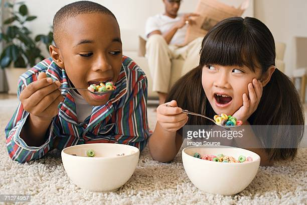 boy and girl lying in living room eating cereal - breakfast cereal stock pictures, royalty-free photos & images
