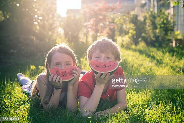 Boy and girl lying on a meadow covering part of her face with slice of watermelon