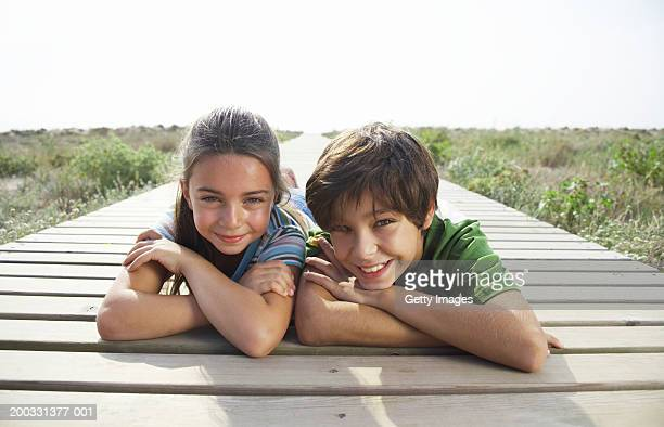 Boy and girl (8-10) lying on beach boardwalk, close-up, portrait