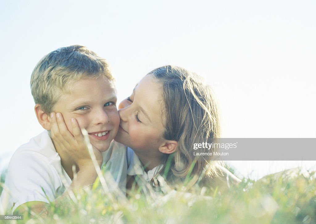 Boy And Girl Lying On Grass Girl Kissing Boy On Cheek -1263