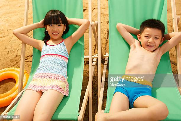 boy and girl lying on sun loungers - chinese bikini girls stock pictures, royalty-free photos & images