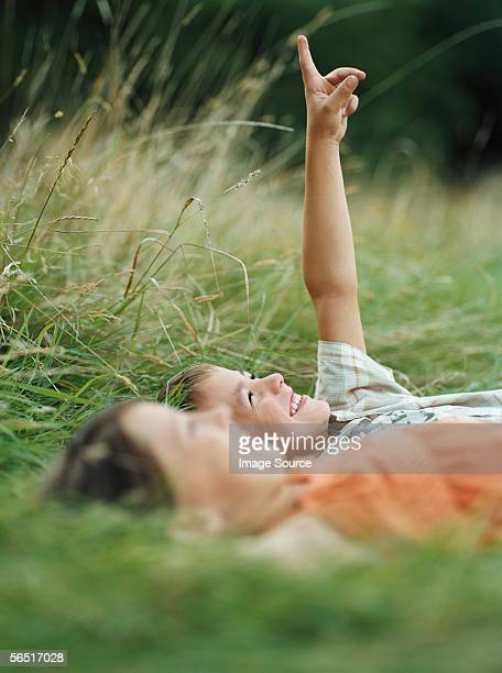 boy and girl lying on the grass - lying down stock pictures, royalty-free photos & images