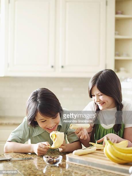 Boy and girl making banana splits.
