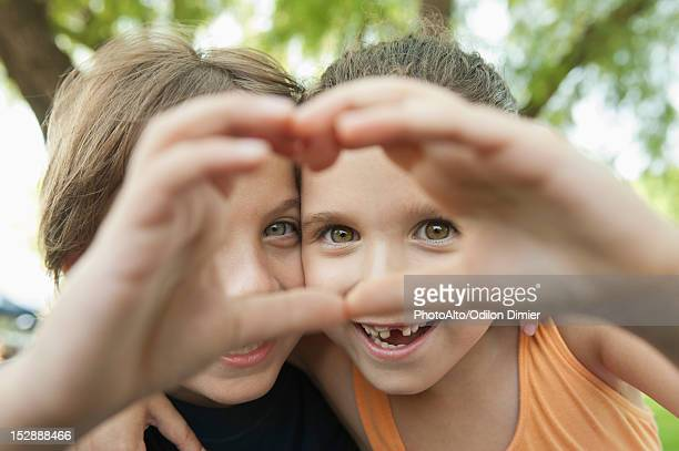 Boy and girl making heart shape with hands