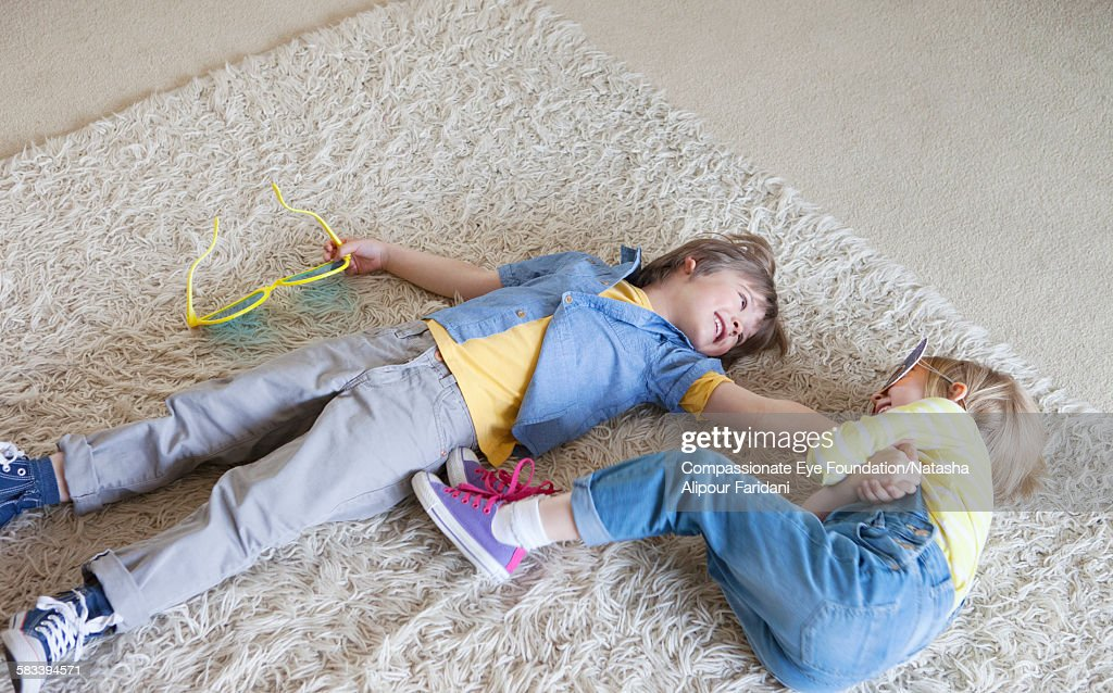 Boy and girl messing about on rug in living room : Stock Photo