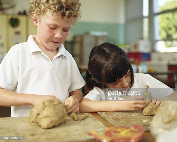 Boy and girl (6-8) modelling clay in classroom