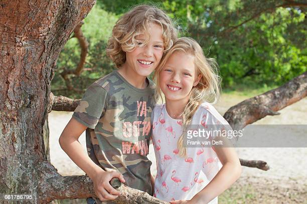 Boy and girl next to tree looking at camera smiling