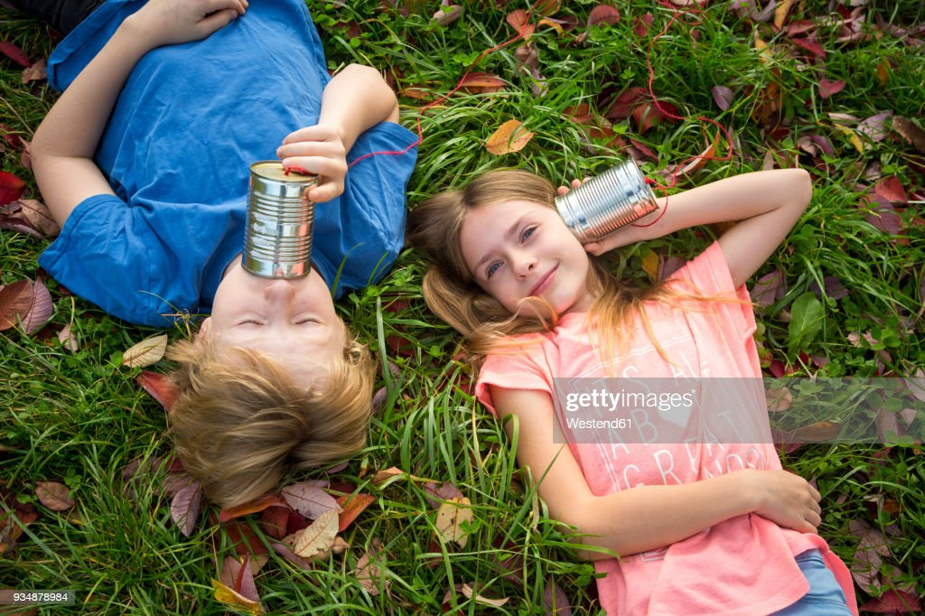 boy and girl on a meadow having fun with tin can phone ストック