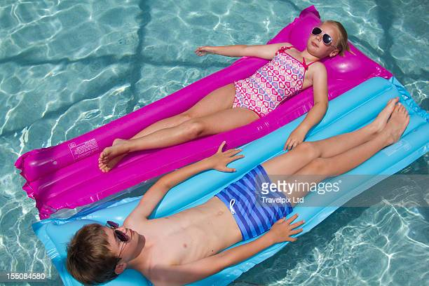 A boy and girl on air mattresses in a pool