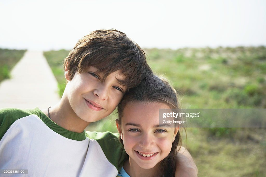 Boy and girl (8-10) on beach boardwalk, close-up, portrait : Stock Photo