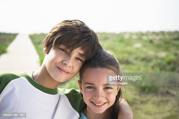 boy and girl (8-10) on beach boardwalk, close-up, portrait - zus stockfoto's en -beelden