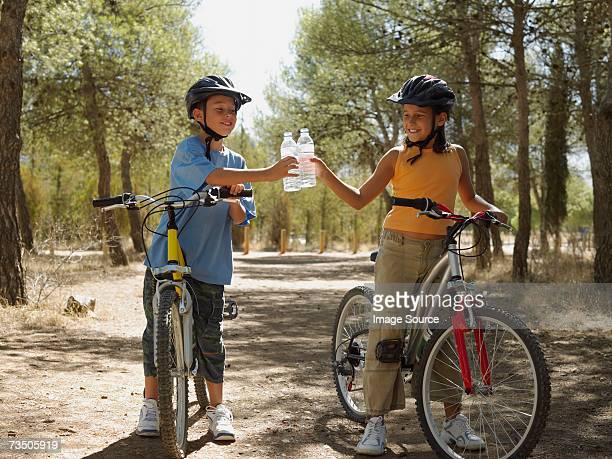boy and girl on bikes with water bottles - cycling helmet stock photos and pictures
