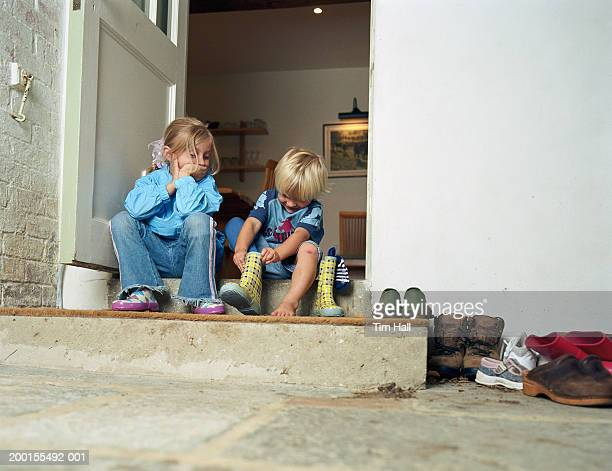 boy and girl (3-5) on doorstep, boy putting on rubber boot - girl mound stock pictures, royalty-free photos & images