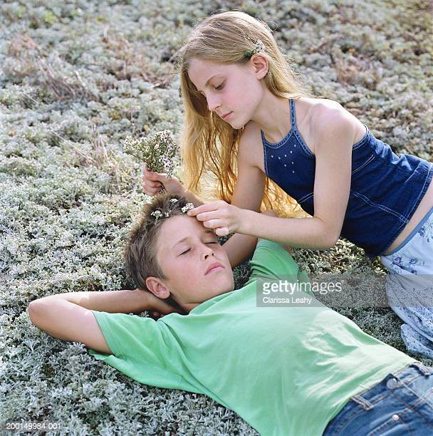 Boy and girl (11-13) on ground, girl placing heather in boy's hair