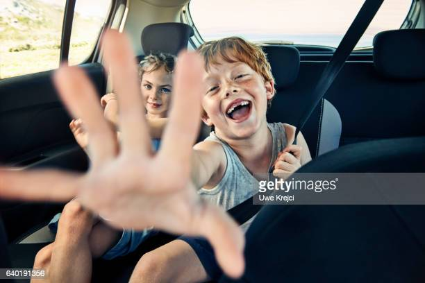 Boy and girl on rear seat of car