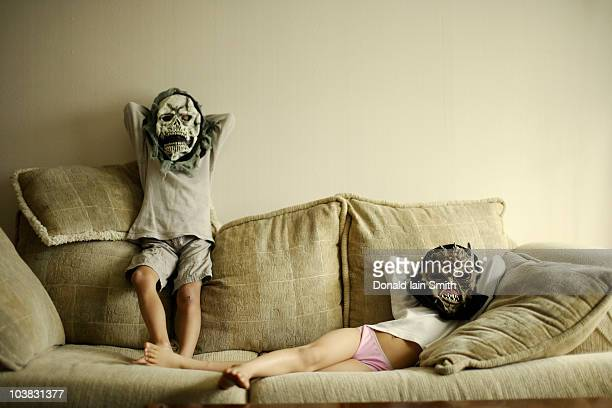 Boy and girl on sofa with scary masks