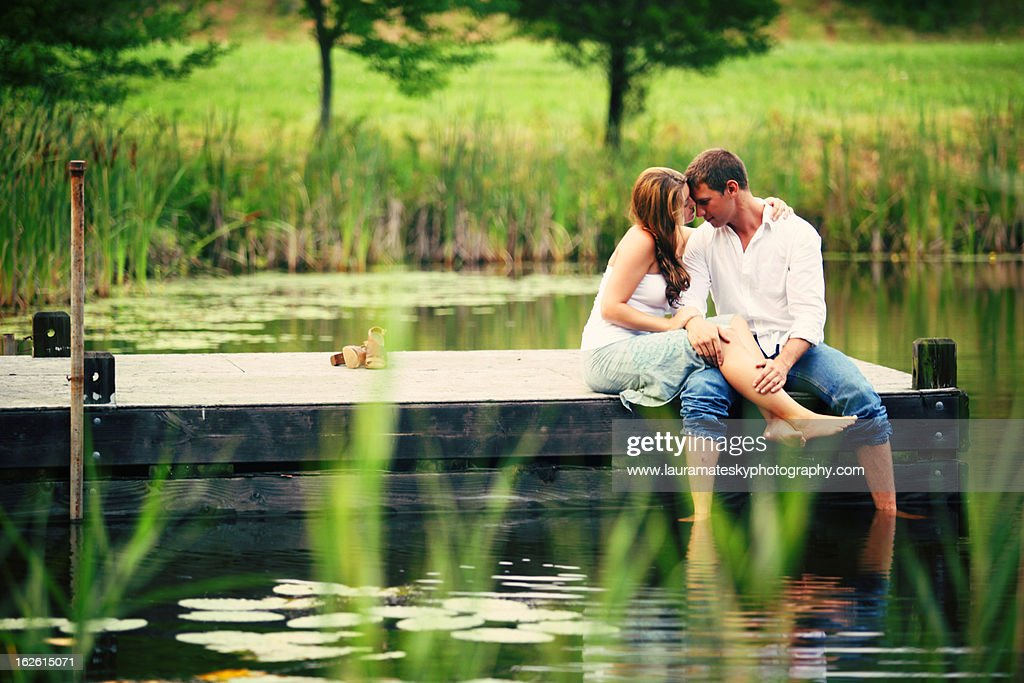 boy and girl on the dock f a pond : Stock Photo