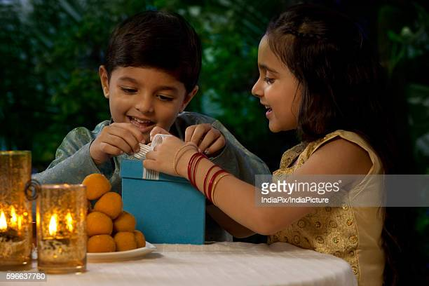 Boy and girl opening gifts on Diwali