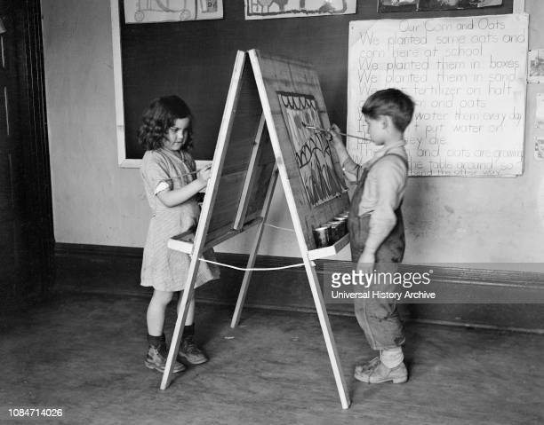 Boy and Girl Painting on Classroom Easel, Reedsville, West Virginia, USA, Elmer Johnson, Farm Security Administration, April 1935.