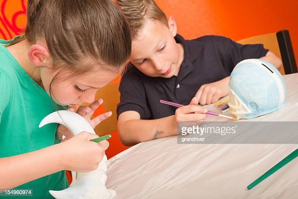 Boy and Girl Painting Pottery
