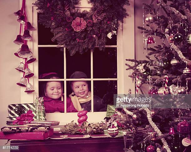 Boy and girl peeking in window, looking at decorated Christmas tree. (Photo by H. Armstrong Roberts/Retrofile/Getty Images)