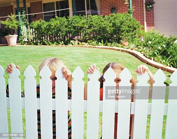 Boy (7-9) and girl (5-7) peeking through white picket fence, portrait
