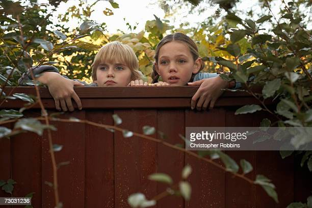 Boy (10-11) and girl (12-13) peeping over fence