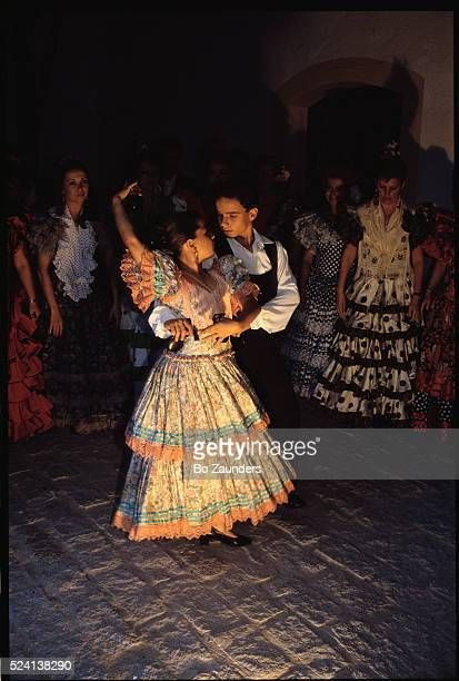 A boy and girl perform a flamenco dance in front of other flamenco dancers in Seville Spain