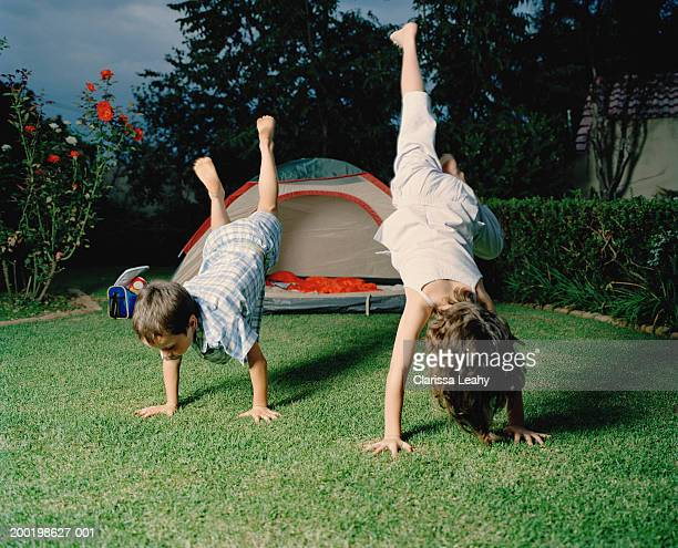 Boy and girl (6-8) performing handstands on grass by tent