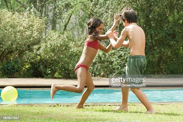 Boy and girl playfighting at poolside