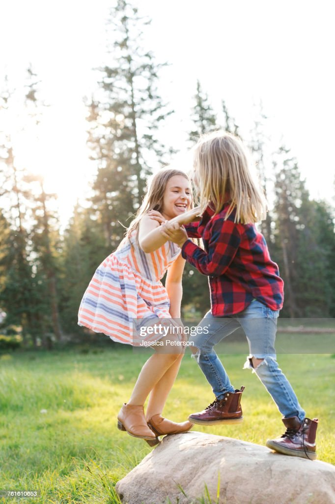 Boy (6-7) and girl (8-9) play-fighting in forest : Stock Photo
