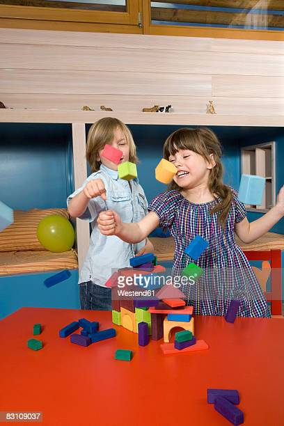Boy and girl (6-9) playing with building blocks