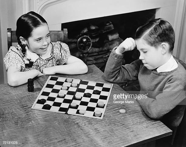 Boy and girl (8-9) playing checkers (B&W), elevated view