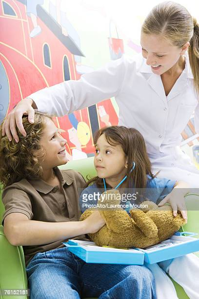 Boy and girl playing doctor with teddy bear while nurse watches