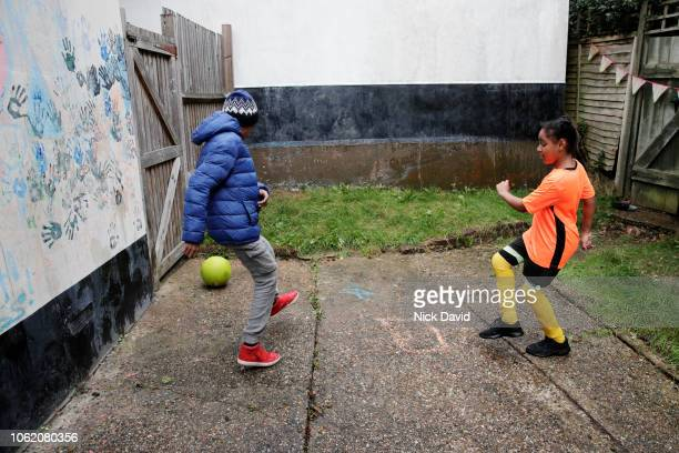 boy and girl playing football in backyard - sporting term stock pictures, royalty-free photos & images