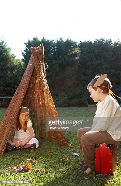 boy and girl (6-7) playing in garden - kampeertent stockfoto's en -beelden