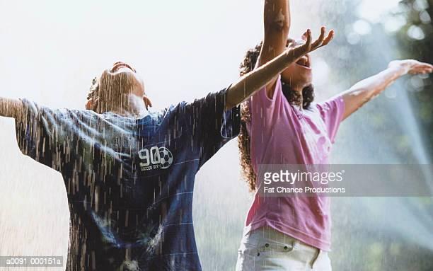 Boy and Girl Playing in Rain