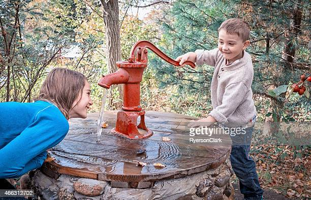Boy and Girl Playing in Water at an Antique Pump.