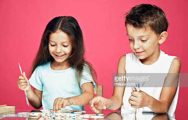 Boy and girl (4-6) playing mikado and smiling
