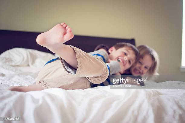 Boy and girl playing on bed