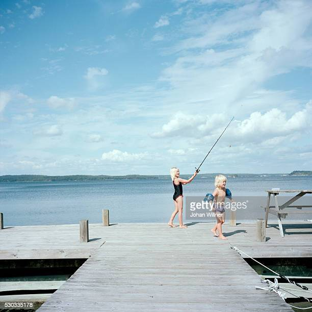 Boy and girl playing on jetty