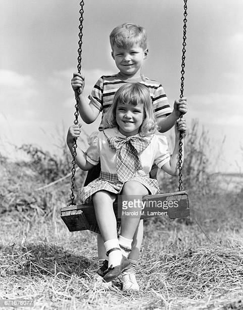 boy and girl playing on swing - {{ collectponotification.cta }} foto e immagini stock