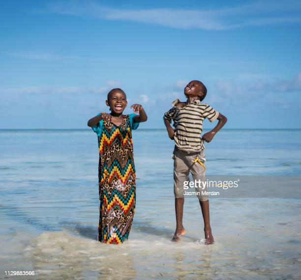 boy and girl playing on the beach - tanzania stock pictures, royalty-free photos & images