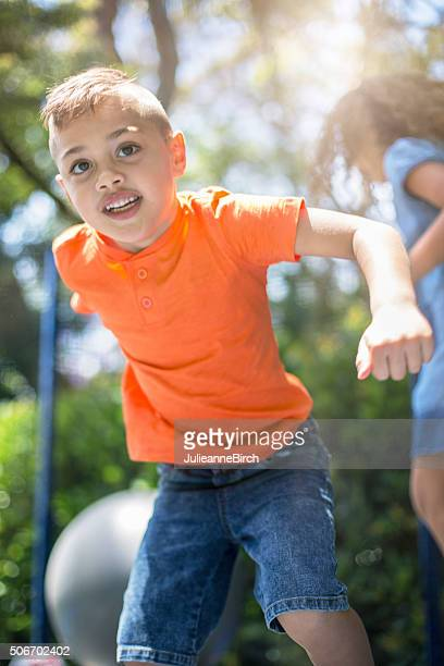 Boy and girl playing on trampoline