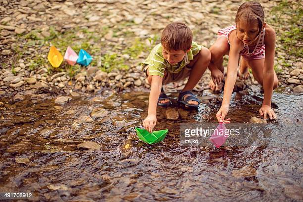 Boy and girl playing paper boats on the river